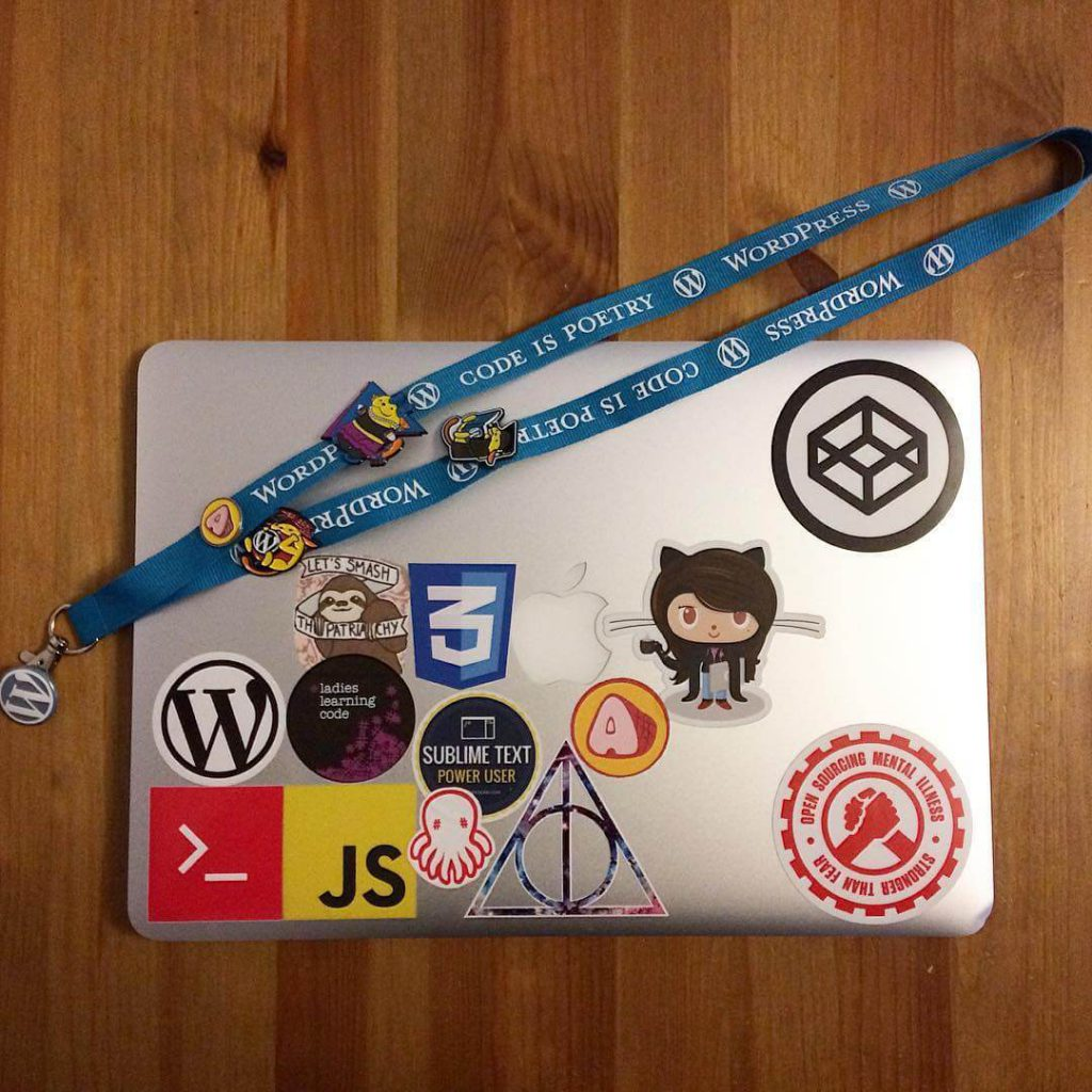 aerial shot of closed laptop covered in stickers with WordCamp lanyard draped across