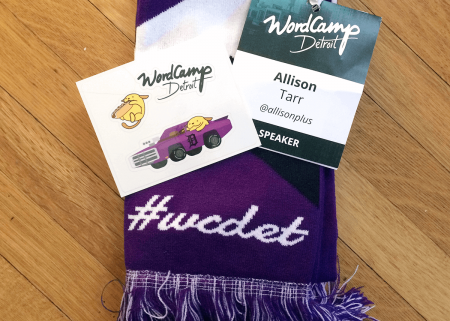WordCamp Detroit purple scarf, name badge, and stickers
